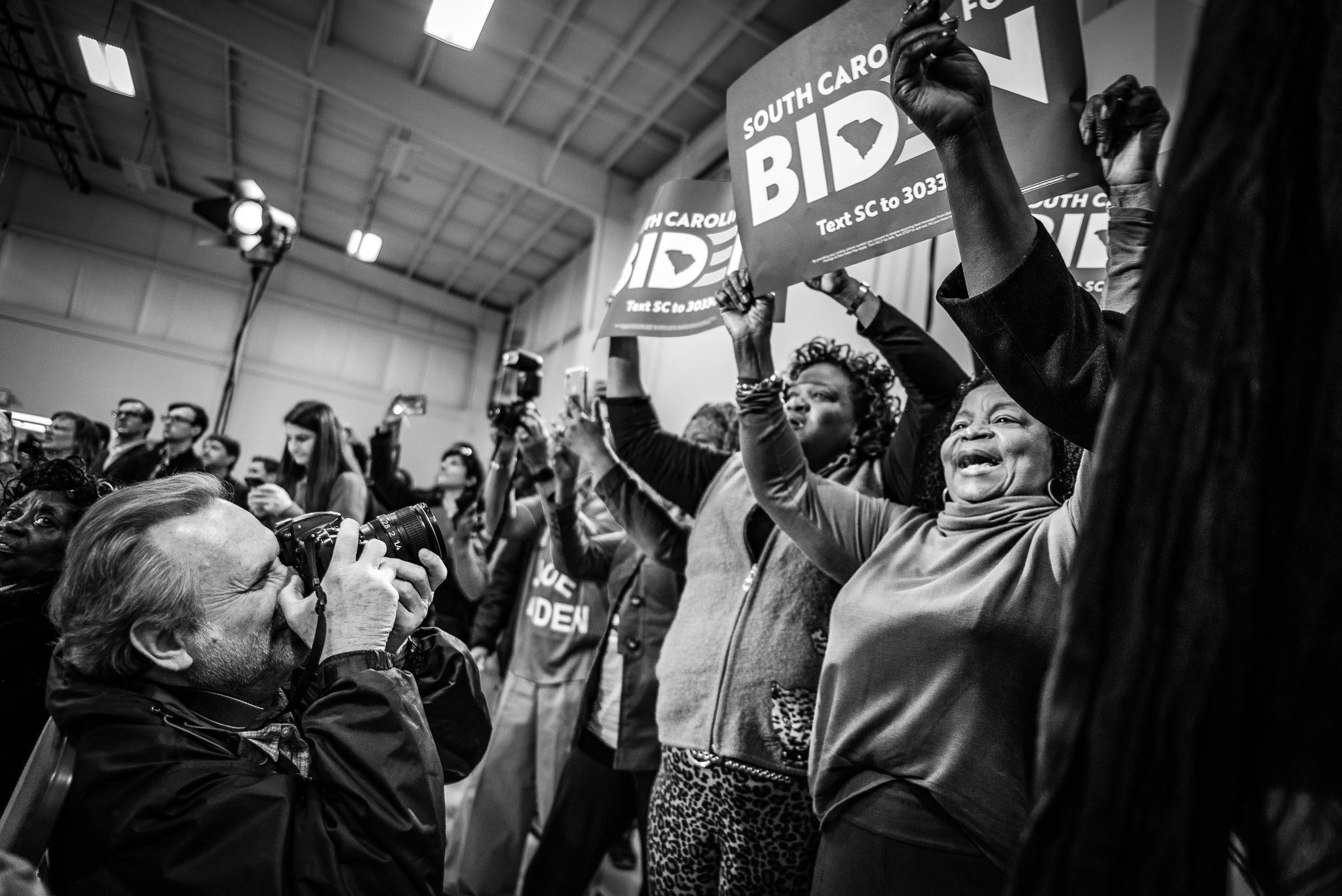 A photographer snaps a photo of a cheering crowd, raising signs at a Joe Biden rally in Sumter, South Carolina. February 28, 2020. Photo: Lance Monotone.