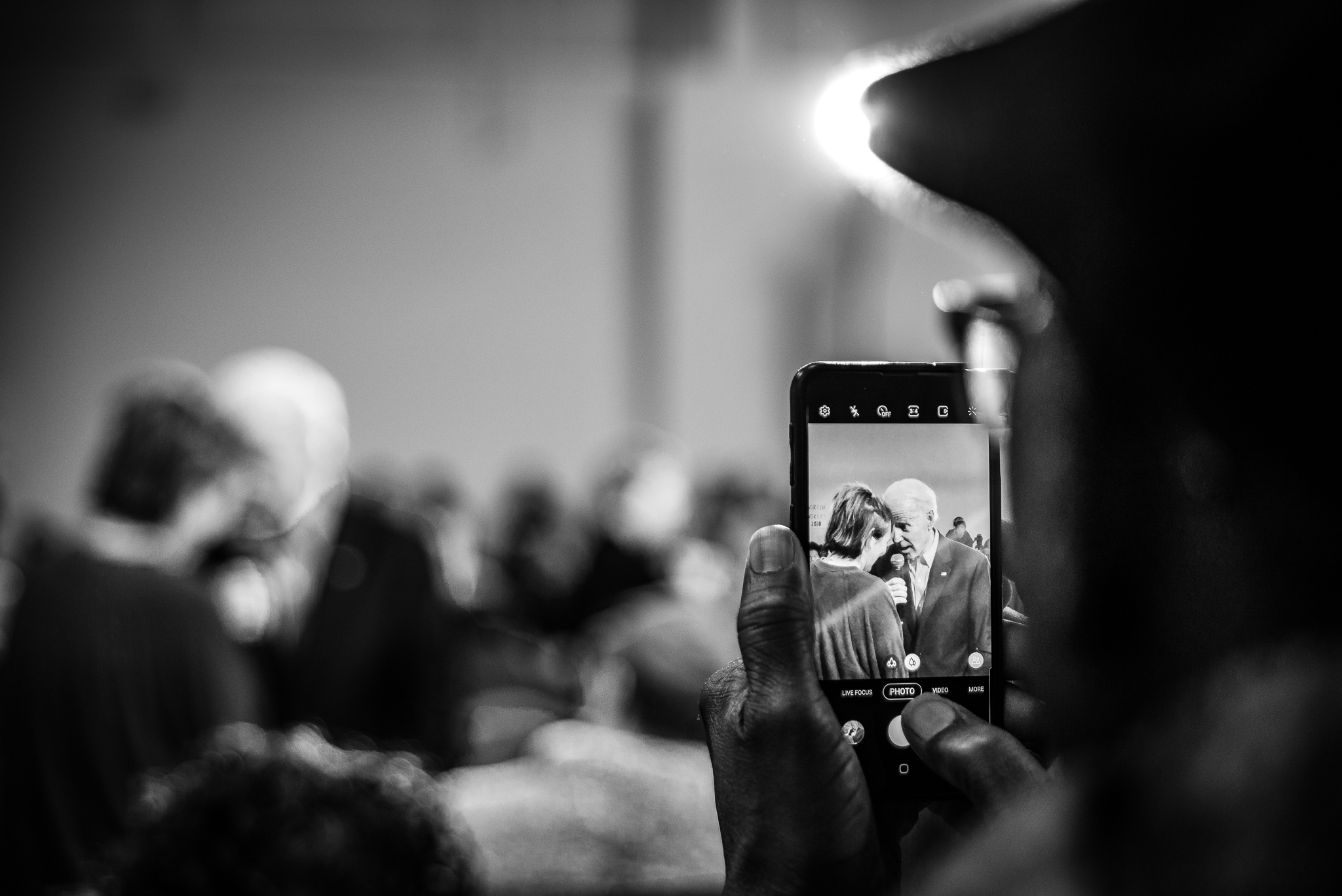 An audience member takes a cell phone photo Joe Biden and Marybeth Berry at a rally in Sumter, South Carolina. February 28, 2020. Photo: Lance Monotone.