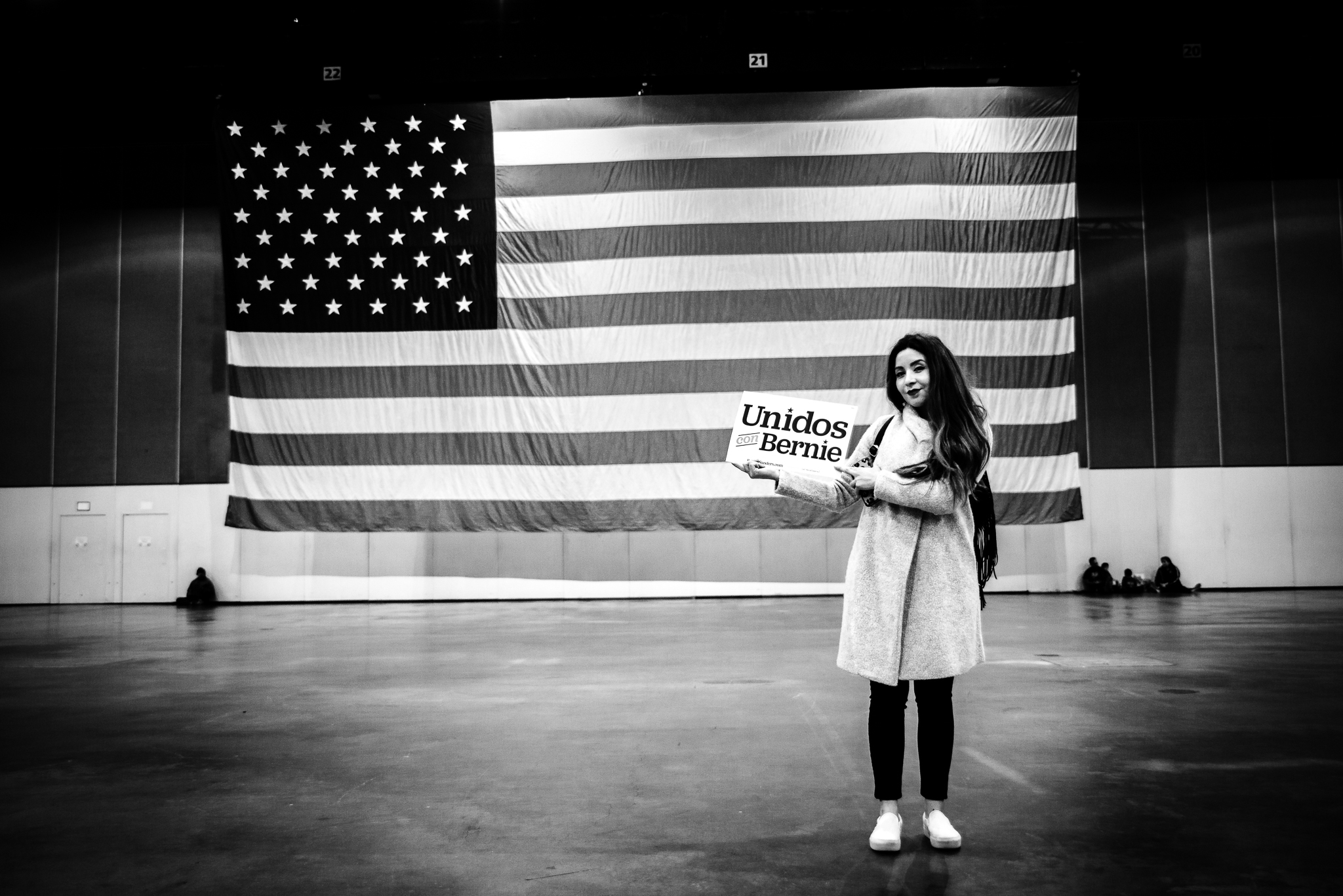 A Bernie Sanders supporter poses in Los Angeles in front of an American flag with a sign that reads: Unidos por Berine. March 1, 2020. Lance Monotone.