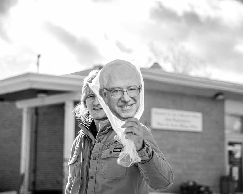 Tyler Tambasco, a travelling political memorabilia salesman, posing with a Bernie Sanders mask in Rochester, New Hampshire. Photo: Lance Monotone.