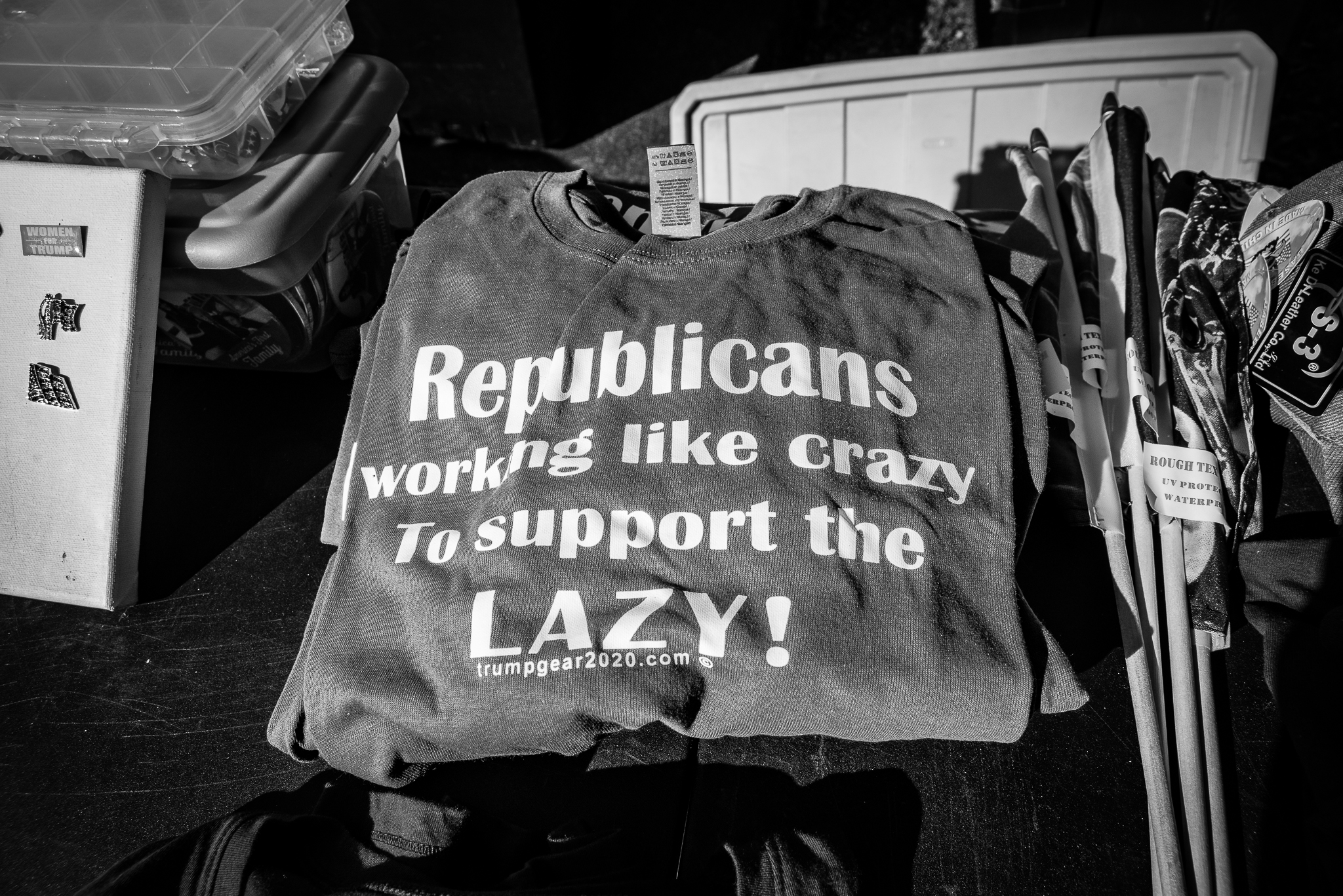 "A t-shirt is displayed on a table next to other Trump memorabilia. It reads, ""Republicans: Working like crazy to support the LAZY!"""