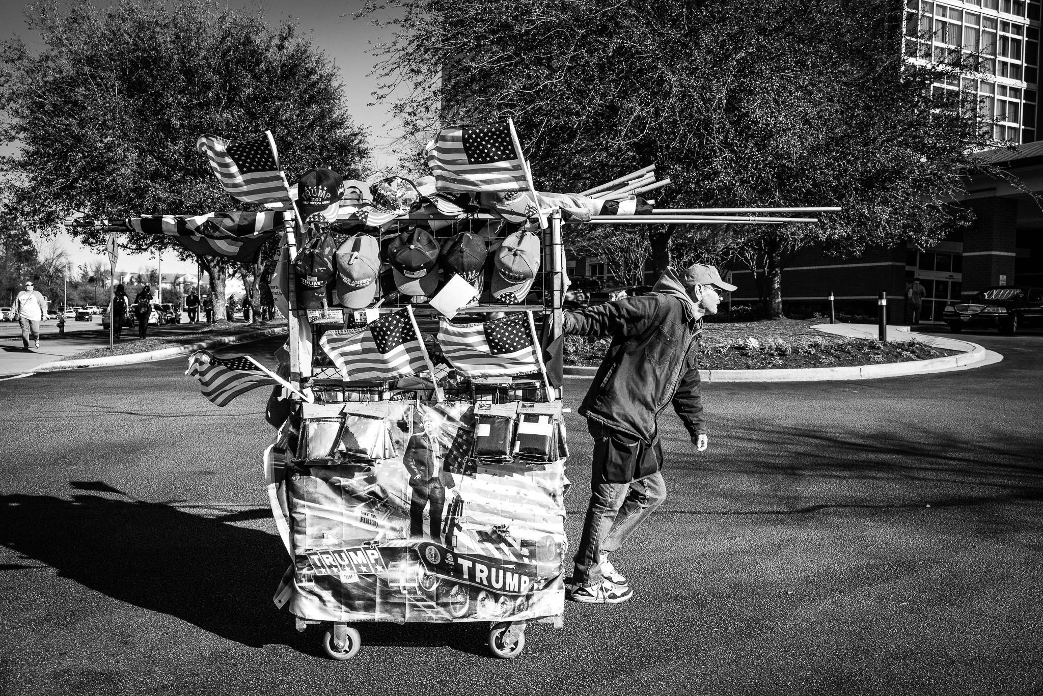 A MAGA merchant pulls his cart across a parking lot at a Trump rally in North Charleston, South Carolina. Photo: Lance Monotone.