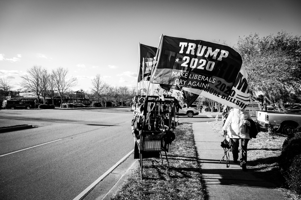 A shopping cart rigged to display MAGA merchandise sits on the side of the road at a Trump rally in South Carolina. Photo: Lance Monotone.